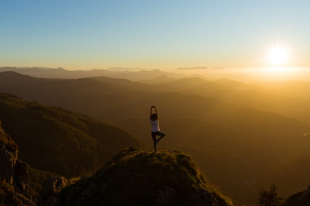 spiritual yoga pose on top of a mountain